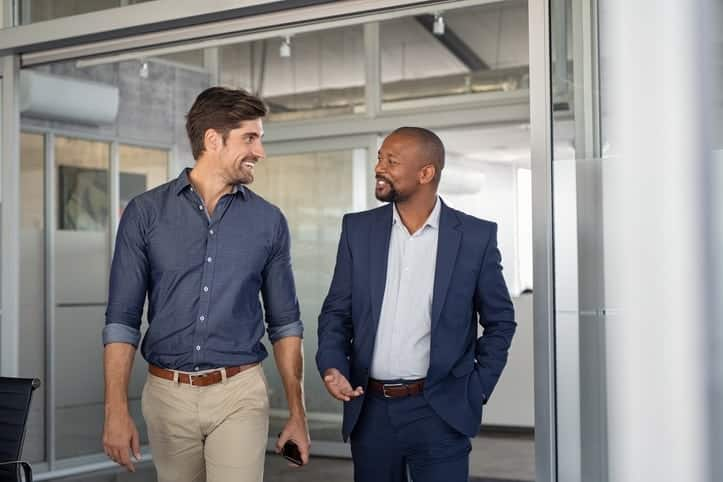 Multiethnic business colleagues walking in office while talking. Two successful business partners in modern office having conversation.
